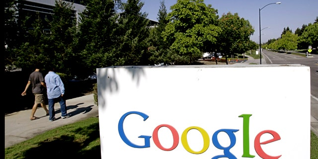 Google workers walk by a sign at company headquarters in Mountain View, Calif.