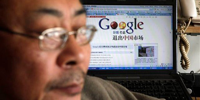 """Award winning Chinese blogger Tiger Temple, or Zhang Shihe, a critic of China's internet censorship, is seen with a webpage with the Chinese words """"Google considers leaving the Chinese market"""" in his home in Beijing, Tuesday, March 23, 2010. Google Inc. stopped censoring the Internet for China by shifting its search engine off the mainland Monday but said it will maintain other operations in the country. (AP Photo/ Gemunu Amarasinghe)"""