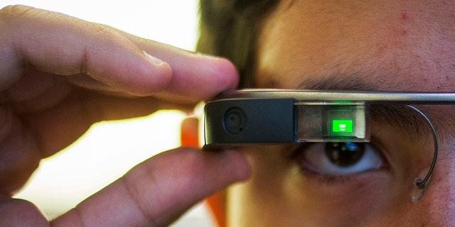 File photo - Tiago Amorim of Brazil, poses with a Google Glass eyewear frame in Manhattan, New York Sep. 19, 2014.