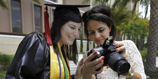 """April 29, 2014: University of South Florida graduating seniors Kyra Ciotti, 22, of Tampa, Fla., left, and Rita Sibaja, 24, of Winter Haven, Fla., look at photos that Rita took of Kyra in her cap and gown Tuesday, April 29, 2014, in Tampa, Fla. The university has banned all self portraits, also known as """"selfies,"""" during their 2014 graduation exercises. (AP/Chris O'Meara)"""