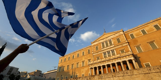 File photo - A protester waves a Greek flag during an anti-austerity rally in Athens, Greece, June 29, 2015.