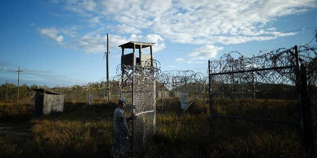 FILE - In this Nov. 13, 2013, file photo reviewed by the U.S. military, a soldier closes the gate at the now abandoned Camp X-Ray, which was used as the first detention facility for al-Qaida and Taliban militants who were captured after the Sept. 11 attacks at Guantanamo Bay Naval Base, Cuba.  During six years behind bars at Guantanamo Bay, Abdul Rauf insisted he was a lowly Taliban foot soldier, even though he was really a corps commander. Rauf was released in 2007 and sent home to Afghanistan. He was working as the top recruiter in Afghanistan for Islamic State militants when a drone strike on Feb. 9, 2015, killed him along with seven others.  (AP Photo/Charles Dharapak, File)