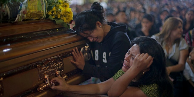 Two unidentified relatives weep in front of the coffin of a person that died during a bus crash a day earlier during a mass at the church in the town of San Martin Jilotepeque, Guatemala, Tuesday, Sept.10, 2013. The death toll in a rural Guatemala bus crash rose to 46 on Tuesday, after two more people died of injuries suffered in the vehicle's plunge into a deep canyon. (AP Photo / Luis Soto)