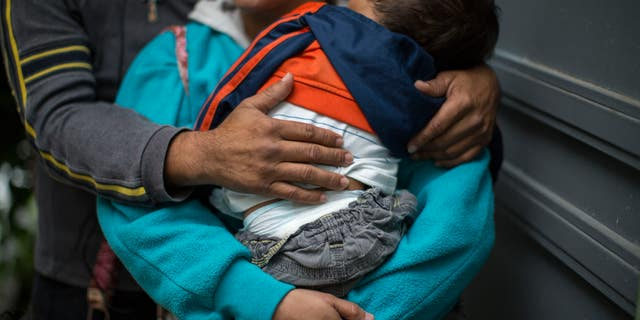 In this June 19, 2014 photo, a Honduran man hugs his wife as she carries their son at a immigrant shelter in Guatemala City.