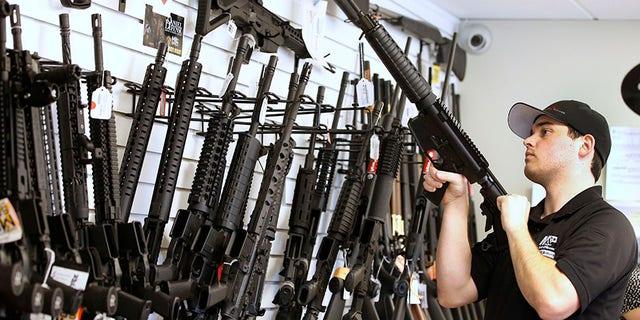 "Salesman Ryan Martinez clears the chamber of an AR-15 at the ""Ready Gunner"" gun store In Provo, Utah, U.S. in Provo, Utah, U.S., June 21, 2016. REUTERS/George Frey - S1AETLGJCGAB"