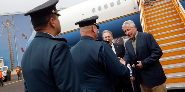 U.S. Defense Secretary Chuck Hagel shakes hands with military officers upon arriving in Mexico City Wednesday, April 23, 2014. (AP Photo/Shannon Stapleton, Pool)