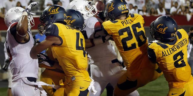 In this Sept. 20, 2014, photo, Arizona running back Austin Hill, center in white, catches a pass for a touchdown in the middle of California defenders including Kenny Lawler (4), Griffin Piatt (26) and Darius Allensworth (2) with no time left on the clock at Arizona Stadium in Tucson, Ariz. Anu Solomon hit Hill with the 47-yard Hail Mary to send the stunned Bears to a 49-45 loss. One part planning and two parts_ at least_ luck, that desperation heave to the end zone rarely results in a touchdown. (AP Photo/Arizona Daily Star, Kelly Presnell )  ALL LOCAL TELEVISION OUT; PAC-12 OUT; MANDATORY CREDIT