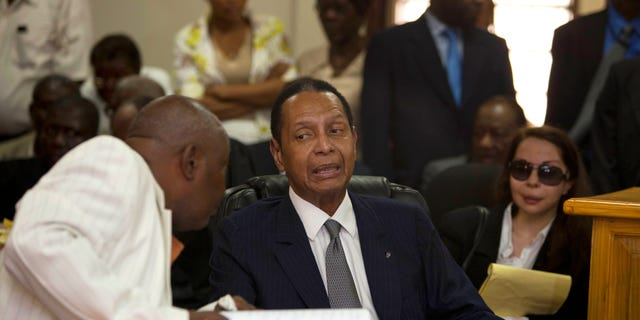 """Feb. 28, 2013: Former Haitian dictator Jean-Claude Duvalier, known as """"Baby Doc,"""" center, attends his hearing as his companion Veronique Roy sits behind, right, inside a courthouse in Port-au-Prince, Haiti."""