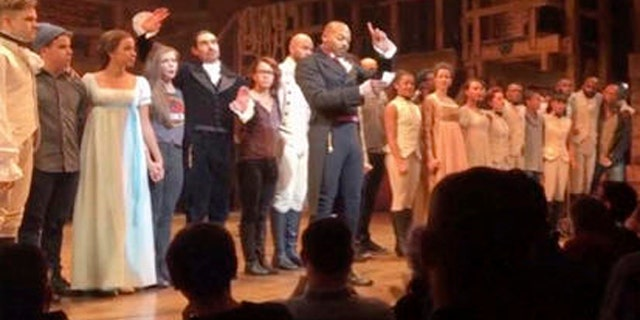 """In this image made from a video provided by Hamilton LLC, actor Brandon Victor Dixon who plays Aaron Burr, the nations third vice president, in """"Hamilton"""" speaks from the stage after the curtain call in New York, Friday, Nov. 18, 2016. Vice President-elect Mike Pence is the latest celebrity to attend the Broadway hit """"Hamilton,"""" but the first to get a sharp message from a cast member from the stage. (Hamilton LLC via AP)"""