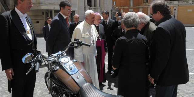 "In this June 12, 2013 photo provided by the Vatican paper L'Osservatore Romano, Pope Francis stands by a Harley-Davidson he was donated, at the Vatican. A 1,585cc Harley-Davidson Dyna Super Glide, donated to Pope Francis last year and signed by him on its tank, will be sold at auction in Paris to help raise funds for a soup kitchen and hostel for the homeless in Rome. Bonhams, noting in a statement Monday Francis' ""preference for modest modes of transport,"" says it will also be auctioning off on Feb. 6 a Harley-Davidson 110th anniversary leather motorcycle jacket, size XL, donated to and signed by Francis. The auction sales will raise money for Caritas Roma, a Catholic charity based in Rome. (AP Photo/L'Osservatore Romano)"