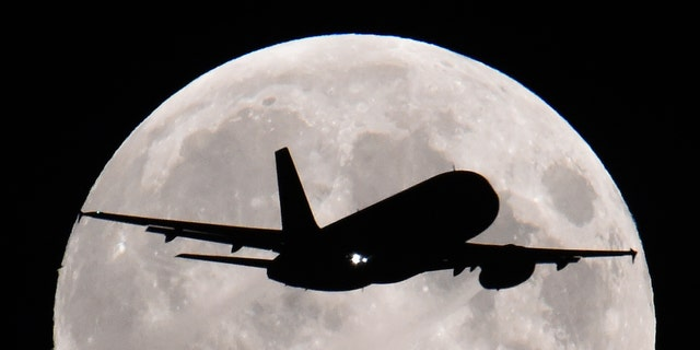 A passenger aircraft descends towards Heathrow Airport with a full moon seen behind in west London- File