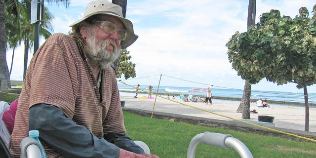 September 8, 2014: Jim Trevarthen, 62, watches the surfers near Waikiki Beach in Honolulu. Trevarthen is one of many homeless people who are unhappy with the city's proposals to ban sitting and lying down on sidewalks in the tourist mecca. (AP Photo/Cathy Bussewitz)