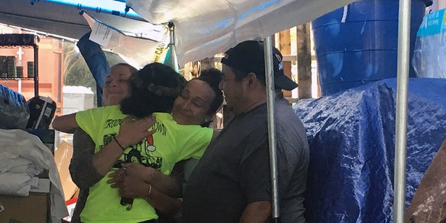 Keala Martins-Keliihoomalu, a 27-year-old full-time student at the University of Hawaii at Hilo who helped organize the Pu'uhonua o Puna community donation center, hugs two people who came to the center.