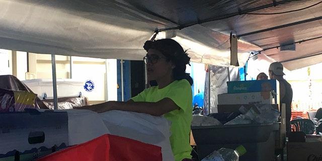 Keala Martins-Keliihoomalu under a tarp tent, opening boxes of donations.