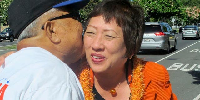 FILE: Aug. 4, 2014: Democratic Rep. Colleen Hanabusa, right, greets a supporter while campaigning for Senate in Honolulu, Hawaii.