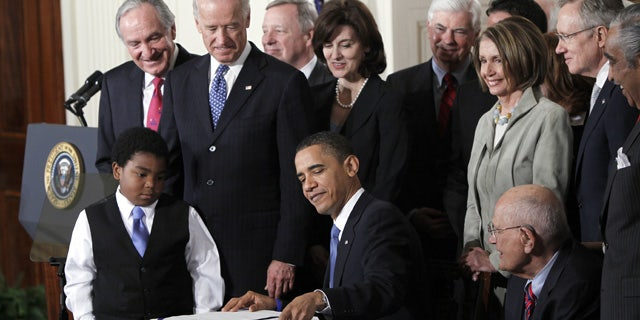 FILE - In this March 23, 2010, file photo, President Barack Obama reaches for a pen to sign the health care bill in the East Room of the White House in Washington. (AP Photo/Charles Dharapak, File)