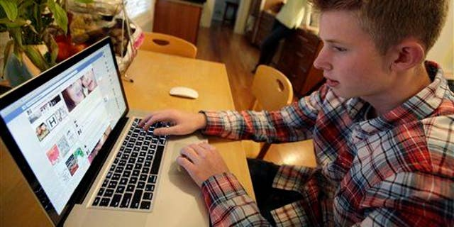 In this Oct. 24, 2013 photo, Mark Risinger, 16, checks his Facebook page in Glenview, Ill.