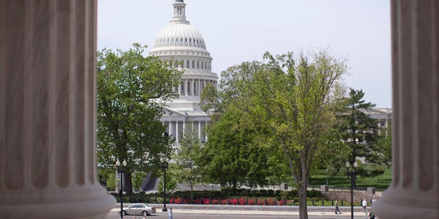 FILE - In this May 5, 2014, file photo, the U.S. Capitol building is seen through the columns on the steps of the Supreme Court in Washington. (AP Photo/Carolyn Kaster, File)