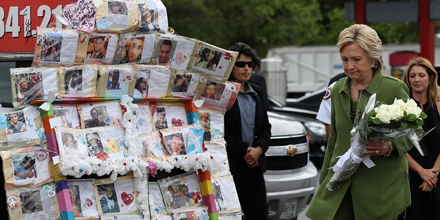 ORLANDO, FL - JULY 22:  Democratic presidential candidate former Secretary of State Hillary Clinton visits a memorial outside of the Pulse nightclub where 49 people were shot and killed by a gunman in June on July 22, 2016 in Orlando, Florida. With three days to go until the Democratic National Convention, Hillary Clinton is campaigning in Florida.  (Photo by Justin Sullivan/Getty Images)