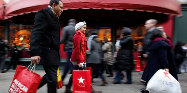 Dec. 18: Shopping bags in hand, consumers walk down 34th Street in New York. Retailers saw a spike in holiday shopping the last weekend before Christmas as retail revenue went up 5.5 percent.