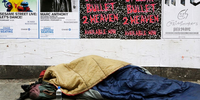 A homeless person sleeps on a sidewalk, Monday, Dec. 21, 2015 in New York. Homeless advocacy groups are threatening legal action against the city over its plans to conduct an aggressive homeless outreach program. The groups say they fear police involvement in the campaign will result in more arrests of homeless people. (AP Photo/Mark Lennihan)