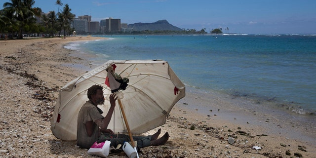 A homeless man drinks water while sitting on the beach at Ala Moana Beach Park located near Waikiki in Honolulu.