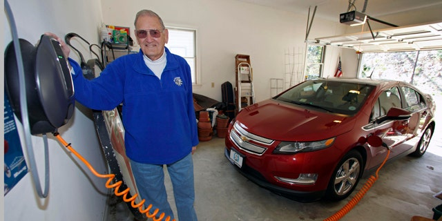 """This Friday, March 25, 2011 photo shows James Brazell as he poses with a charging unit for his Chevy Volt electric car at his home in Asheville, N.C. Brazell plugs the car in after short trips. """"Pretty much I top it up every time I bring it into the garage,"""" he said.    (AP Photo/Chuck Burton)"""