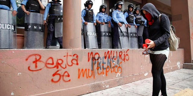 """A protester writes with spray paint """"Berta did not die, she multiplied"""" in front of riot police guarding the attorney general's office in Tegucigalpa, Honduras, Thursday, Oct. 20, 2016. Members of the Civic Council of Popular and Indigenous Organizations of Honduras (COPINH) and people belonging to the Garifuna people protested to demand justice over the March 2016 murder of Honduran indigenous leader and environmentalist Berta Caceres and to halt construction of the Agua Zarca dam, which would displace many of the indigenous Lenca people. (AP Photo/Fernando Antonio)"""