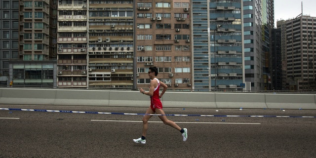 A participant runs past a old residential zone on the Connaught Road West Flyover as he competes in the Hong Kong marathon.