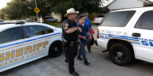 Harris County Sheriff's Department Sgt. D.J. Hilborn, left, escorts a family back to their home near the scene of a multiple shooting Sunday, Aug. 9, 2015, in Houston. Eight people, including five children and three adults, were found dead late Saturday inside a Houston-area home following the arrest of a man who exchanged gunfire with police, Texas authorities said Sunday. (AP Photo/David J. Phillip)