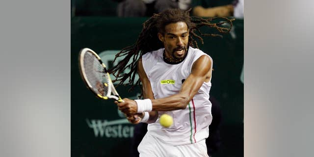 Dustin Brown hits a return against John Isner at the U.S. Men's Clay Court Championship tennis tournament on Wednesday, April 9, 2014, in Houston. (AP Photo/Houston Chronicle, Bob Levey) MANDATORY CREDIT