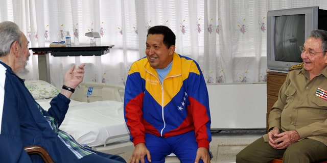 In this June 17, 2011, file photo released by Granma newspaper, Cuba's former President Fidel Castro, left, and his brother, President Raul Castro, right, speak with Venezuela's Hugo Chavez at a Cuban hospital as Chavez recuperates from surgery for a pelvic abscess.