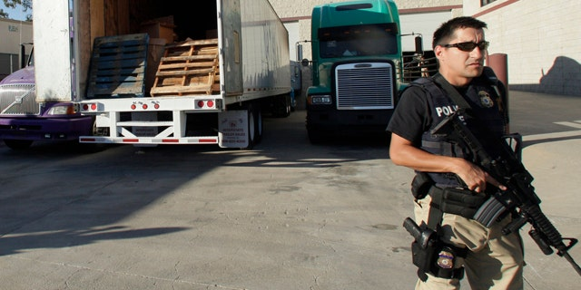 Nov. 3, 2010: John Morton, left, the Director of Immigration and Customs Enforcement inspects a bundle of marijuana with Joe Garcia, assistant agent in charge for Homeland Security Investigations, at a warehouse along the border between the United States and Mexico.