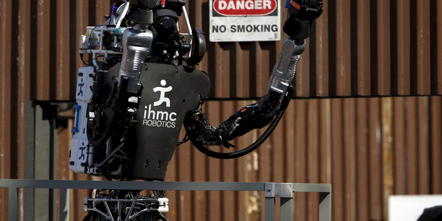 """The Team IHMC Robotics Atlas """"Running Man"""" robot built by Boston Dynamics raises its arms to celebrate after climbing the stairs during the finals of the Defense Advanced Research Projects Agency (DARPA) Robotic Challenge in Pomona, California June 6, 2015."""