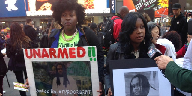 """Qiara Butler, left, and Tawanda Jones demonstrate during a rally against """"police brutality and murder"""" in Times Square on Oct. 22."""