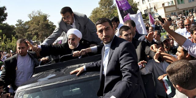 Sept. 28: Iranian President Hassan Rouhani, center, waves to supporters upon his arrival from the US near the Mehrabad airport in Tehran, Iran.