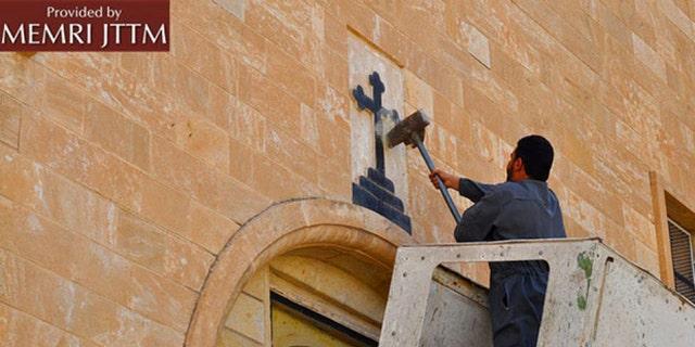 ISIS men destroy various Christian symbols in Nineveh, Iraq.