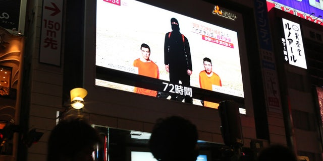 "A TV news program reports two Japanese hostages held by the Islamic State group in Tokyo, Friday, Jan. 23, 2015. Militants affiliated with the Islamic State group have posted an online warning that the ""countdown has begun"" for the group to kill a pair of Japanese hostages. (AP Photo/Eugene Hoshiko)"