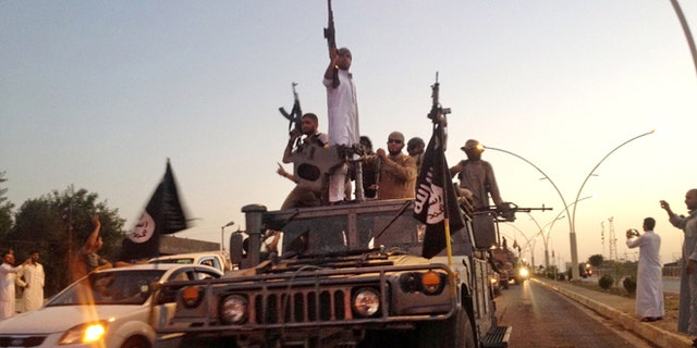 In this file photo taken Monday, June 23, 2014, fighters from the Islamic State group parade in a commandeered Iraqi security forces armored vehicle down a main road at the northern city of Mosul, Iraq.