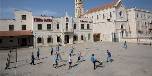FILE - In this Tuesday, May 26, 2015 file photo, Arab Israeli Christian school children play soccer at the Terra Santa School in the mixed Jewish-Arab city of Ramle, Israel. About 2,500 striking demonstrators gathered Sunday, Sept. 6, 2015, outside the prime minister's office in Jerusalem, police said, to protest against the slashing of funds for Christian schools. Christian school administrators accuse Israel of cutting their funding as a tactic to pressure them to join the Israeli public school system _ a move they say would interfere with the schools' Christian values and high academic achievements. (AP Photo/Oded Balilty, File)