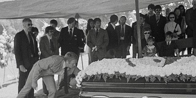 Steve McQueen pays respect to Bruce Lee's casket.
