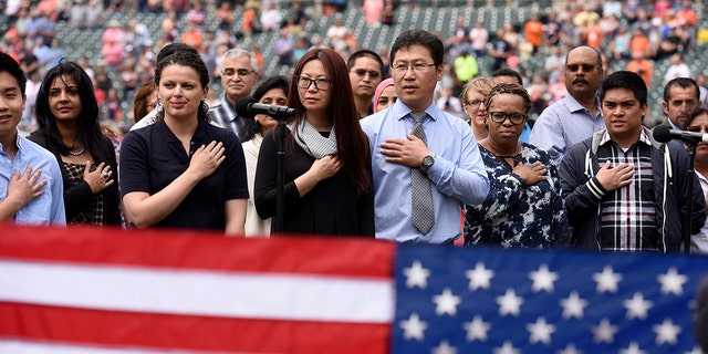 """Thirty-two Southeast Michigan immigrants recite the """"Pledge of Allegiance"""" as they are sworn in to become United States citizens during a naturalization ceremony prior to a baseball game between the Detroit Tigers and the Kansas City Royals, Thursday, June 29, 2017, in Detroit. This is the 10th year the ceremony has taken place at Comerica Park during the baseball season."""