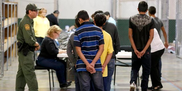 Boys wait in line to make a phone call as they are joined by hundreds of mostly Central American immigrant children that are being processed and held at the U.S. Customs and Border Protection Nogales Placement Center on Wednesday, June 18, 2014, in Nogales, Ariz.