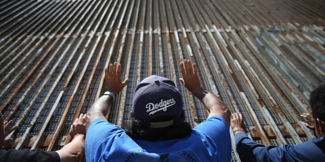 """TIJUANA, MEXICO - MAY 01:  Immigrant advocacy members pray at the U.S.-Mexico border fence on May 1, 2016 in Tijuana, Mexico. Mexicans on the Tijuana side can approach the border fence at any time. The U.S. Border Patrol, however, tightly controls the San Diego, CA side and allows visitors to speak to loved ones through the fence during specific weekend hours at """"Friendship Park,"""" which straddles the border. The park is the only place along the 1,954-mile border where such interactions are permitted by U.S. authorities. On only three occassions have U.S. officials allowed a gate to be opened at the park for pre-screened separated family members to embrace.  (Photo by John Moore/Getty Images)"""