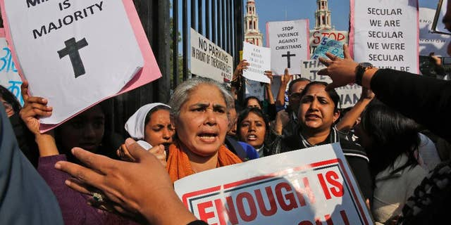 Indian Christians hold placards protesting against attacks on churches in the Indian capital as they assemble outside the Sacred Heart Church in New Delhi, India.