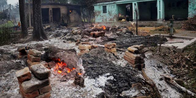 In this Sunday, Jan. 18, 2015 photo, the remains of burnt and ransacked huts still smolder in a village following a clash between two communities in a village, nearly 105 kilometers (65 miles) north of Patna, the Indian capital of Bihar state. At least four Muslims were burned to death Sunday when their thatched huts were set on fire during a clash between Hindu and Muslim groups in a village in eastern India, a government official said. (AP Photo/ Press Trust Of India)  INDIA OUT