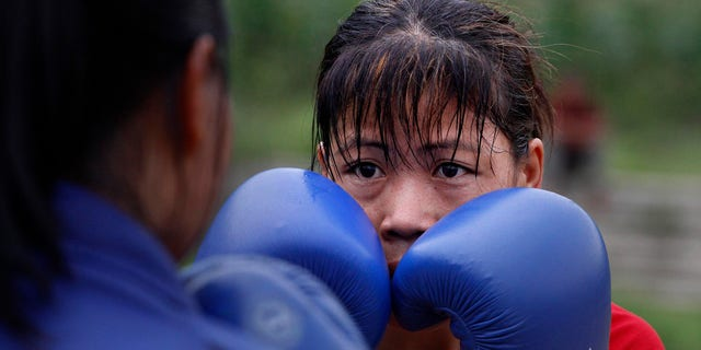 June 14, 2012: In this photo, Indian boxer and five-time world champion Mary Kom, right, practices with her student in Langol Games village on the outskirts of Imphal, India.