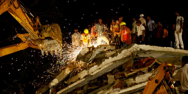 April 4, 2013: Rescue workers look for trapped people after a residential building collapsed in Thane, Mumbai, India.