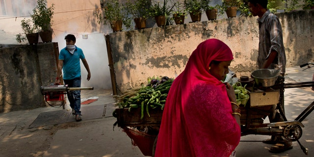 Sept. 16, 2015: A vegetable vendor, right watches as a municipal worker, left, arrives to fumigate a residential area to prevent mosquitoes from breeding in New Delhi, India.