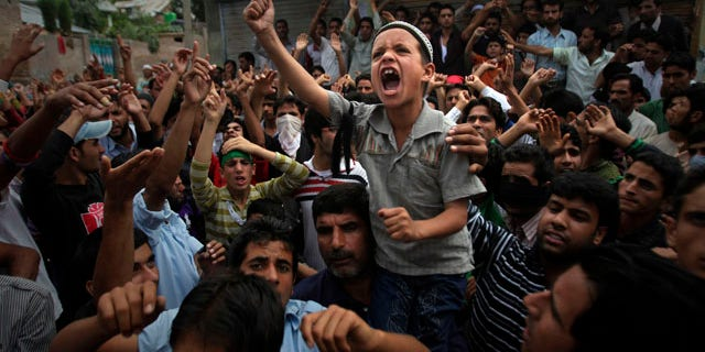 Sept. 13, 2010: A young Kashmiri boy shouts slogans during a protest on the outskirts of Srinagar, India. Indian forces battled Kashmiri protesters in the streets of the disputed territory Monday in demonstrations fueled in part by a report of the Quran being desecrated in the United States.
